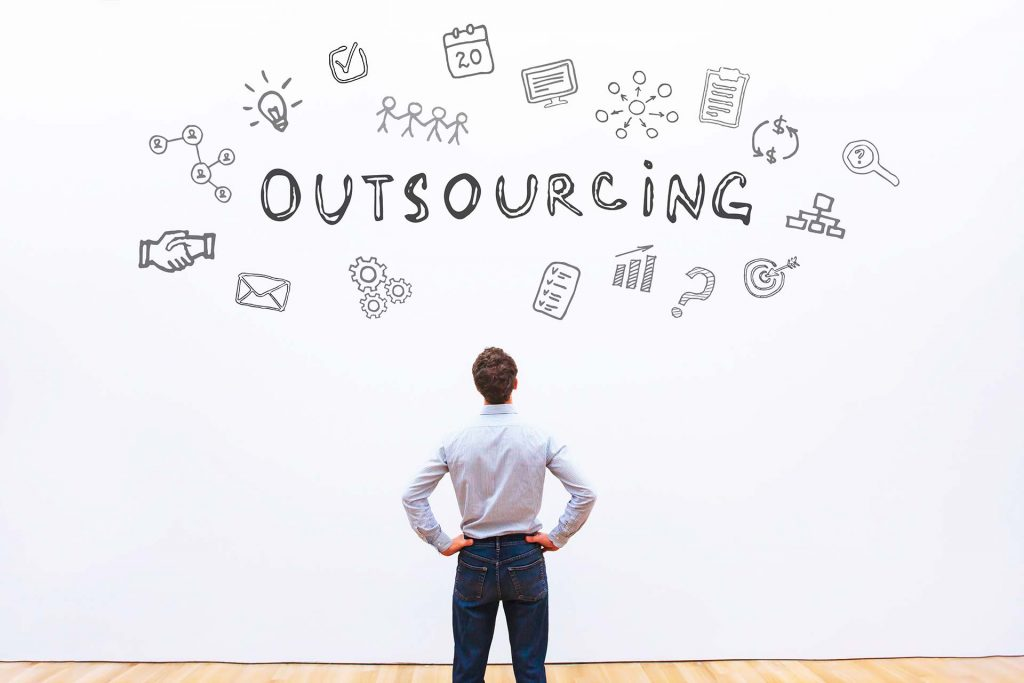 a man standing in front of a wall, looking at his options to outsource data analytics for his company