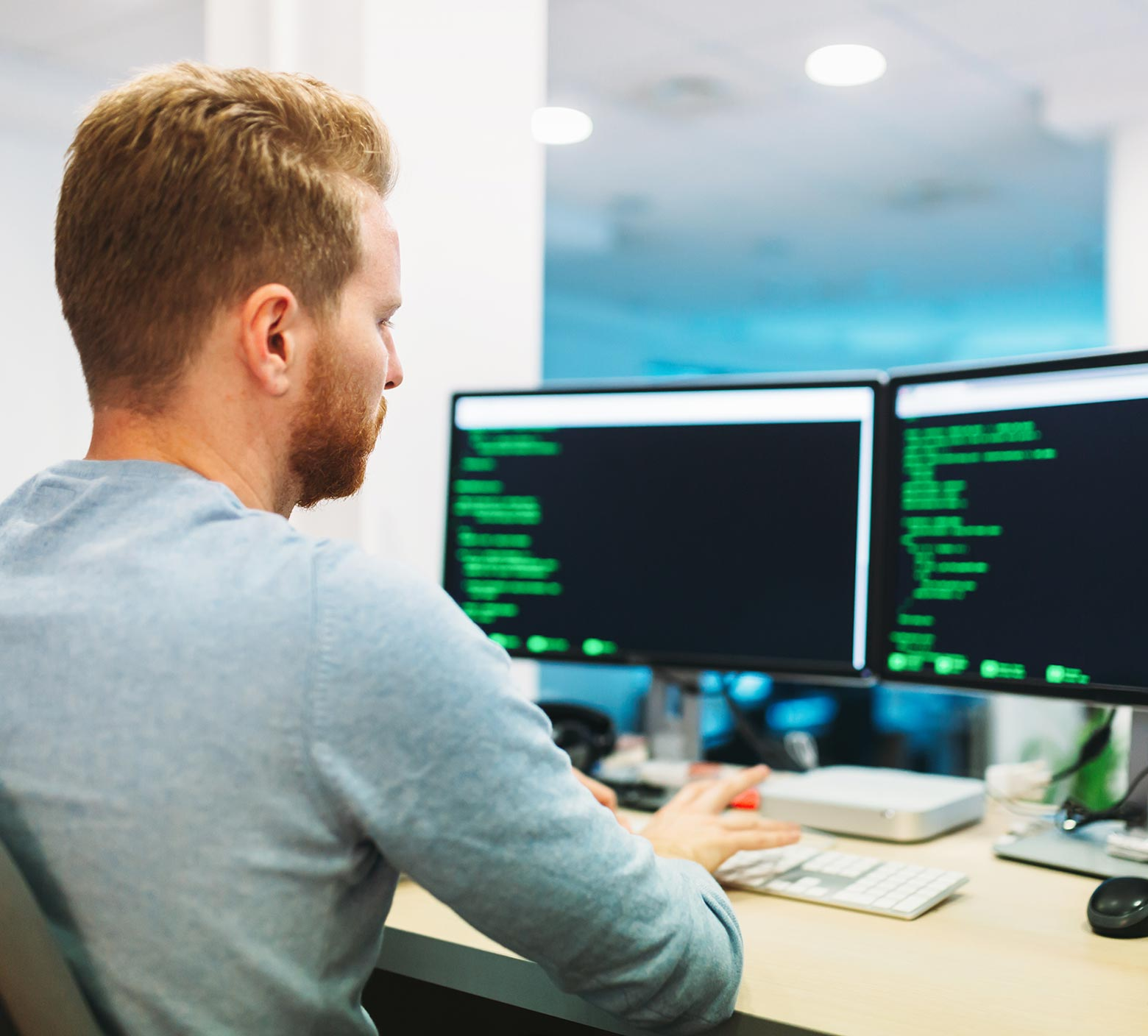 Data Analyst analysing lines of code on his desktop, doing predictive analytics