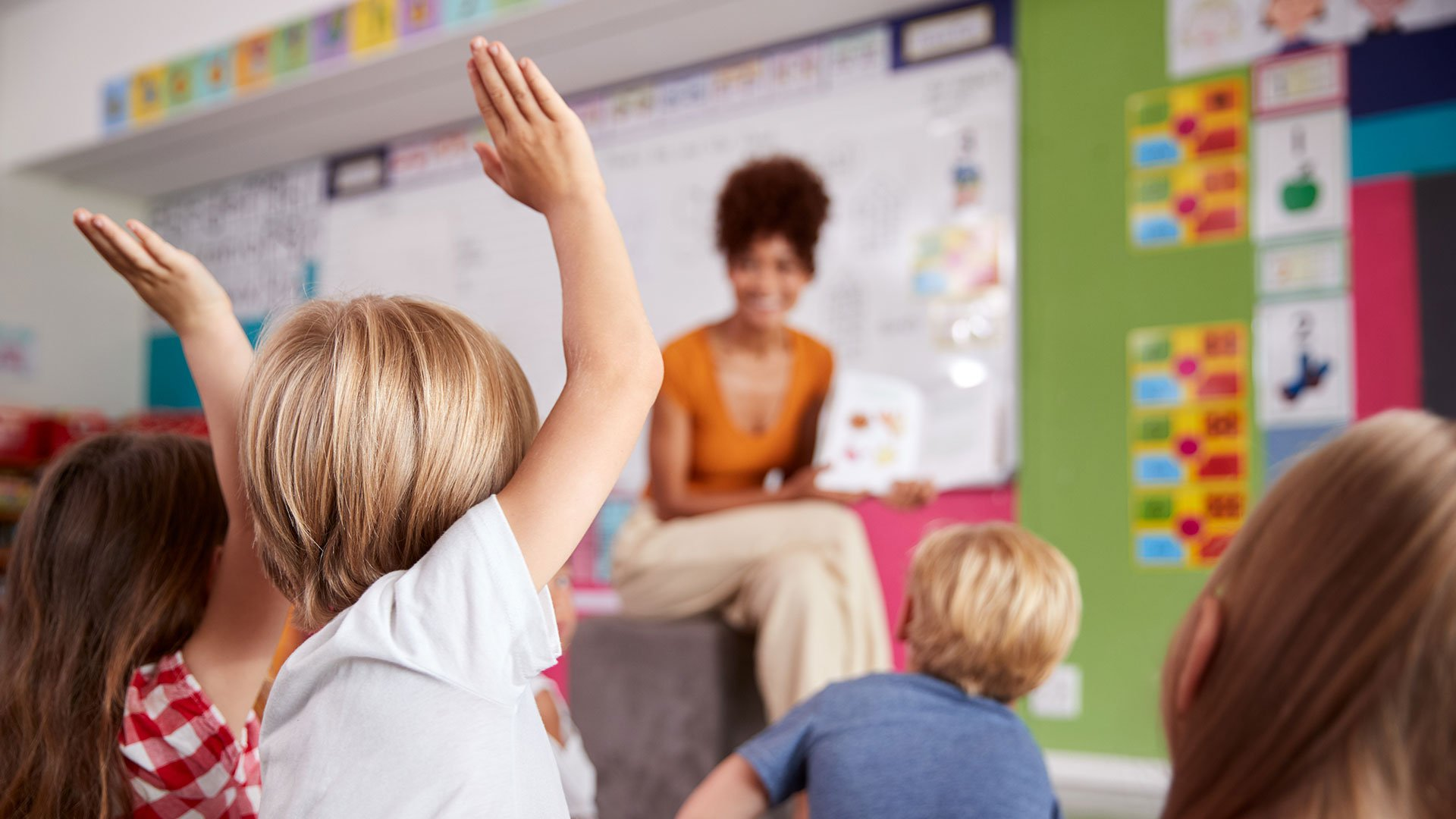 Teacher asking a question about analytics and children raising their hand to answer it.