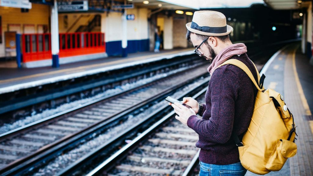 A man standing on a railway platform using his phone conveying how fast viral marketing is.